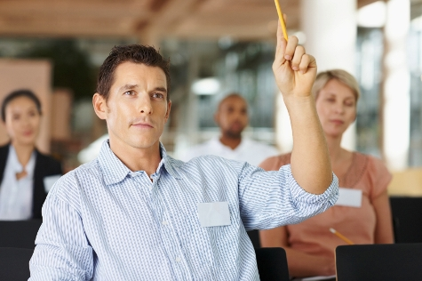 Man asking a question in meeting with colleagues at the back