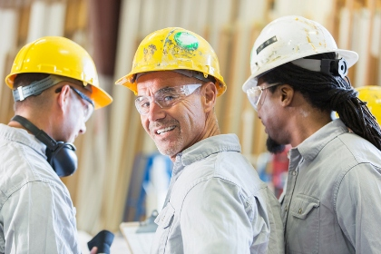 Three men in hard hats working together