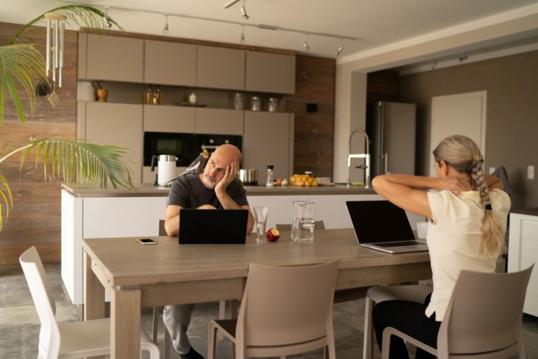 European couple at dining room table with their laptops