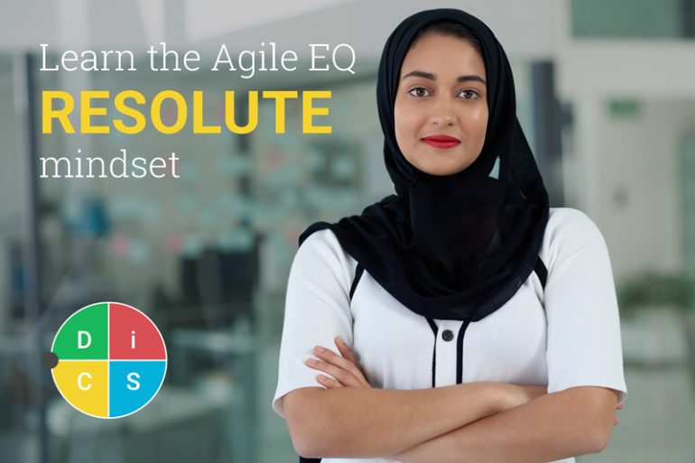Woman in an office looking at the camera with arms crossed. Text reads: Learn the Agile EQ Resolute mindset.
